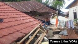 Seorang anak sedang makan diatas puing bangunan rumah yang roboh di desa Kayuangi, Kecamatan Malunda, Kabupaten Majene, Sulawesi Barat. Jumat (28/1/2021). (Foto: VOA/Yoanes Litha)