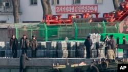朝鲜公民在朝鲜新义州河岸的船上卸货。新义州对面就是中国与朝鲜的边境城市丹东。(资料照。摄于2011年12月30日。)