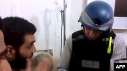 敘利亞活動人士發佈的圖片顯示聯合國檢查人員在莫達米亞西南郊區一家臨時醫院向傷者查問。