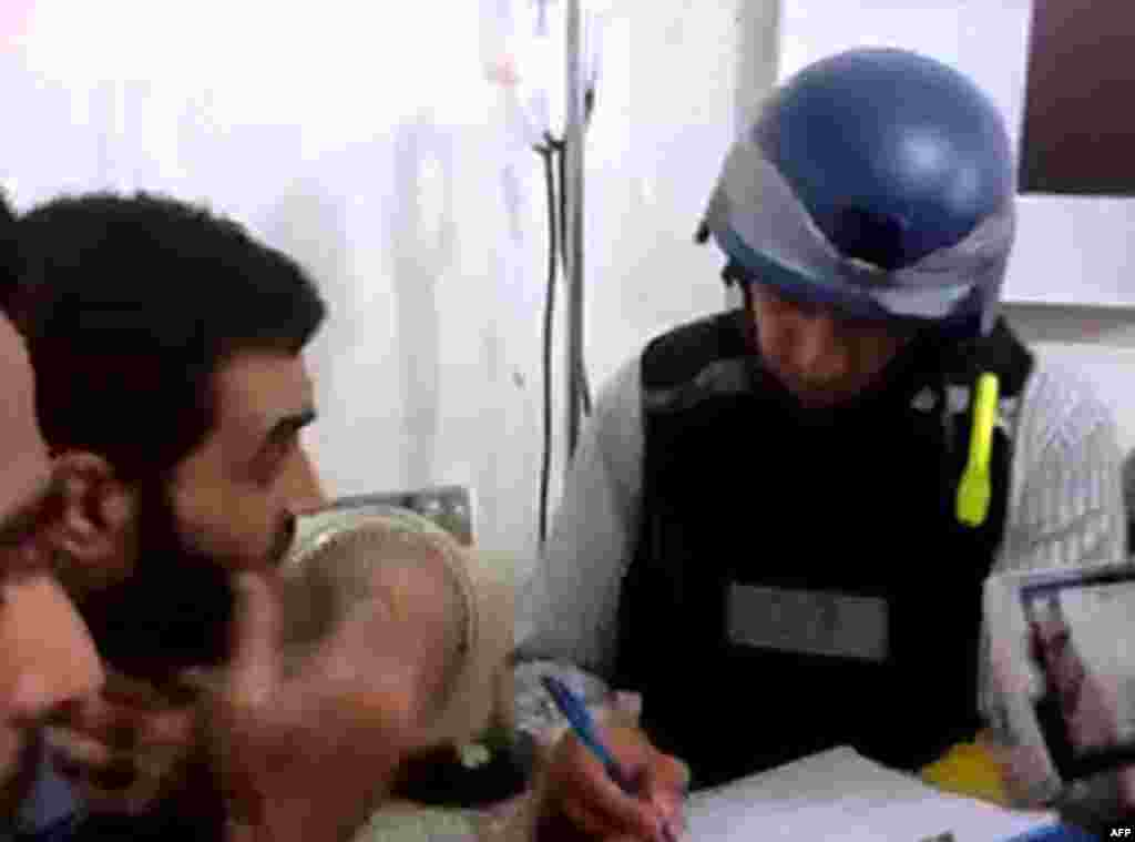 An image grab taken from a video posted by Syrian activists purportedly shows a U.N. inspector speaking to a man in a Damascus suburb, August 26, 2013.