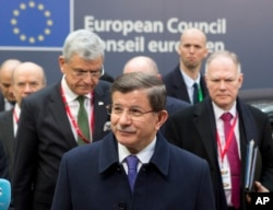 Turkish Prime Minister Ahmet Davutoglu, center, arrives for an EU summit in Brussels on Friday, March 18, 2016.