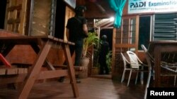 Armed men are seen near a door of a hotel in Sabah, April 2, 2014.