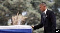 Presiden AS Barack Obama menyentuh peti mati dari mantan Presiden Israel Shimon Peres setelah menyampaikan sambutan pada upacara pemakaman di taman makam nasional Mount Herzl di Jerusalem (30/9). (foto: AP Photo/Carolyn Kaster)