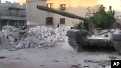 In this image made from amateur video released by the Ugarit News and accessed July 24, 2012, a Free Syrian Army solider drives a Syrian military tank in Aleppo, Syria.