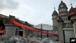 ARSIP – Seorang anggota jemaat gereja di Geraja Kristen Desa Zengshan berdiri dekat tumpukan batu yang ditumpuk di depan gerbang untuk mencegah karyawan pemerintah memasuki halaman untuk merubuhkan salib (16/7/2014). Desa, Zengshan, Provinsi Zhejiang. China. (foto: AP Photo/Didi Tang, dok.)