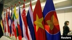 Seorang perempuan berjalan melintas di depan bendera negara-negara anggota ASEAN dalam KTT ASEAN di Suntec Convention Centre di Singapura, 11 November 2018.