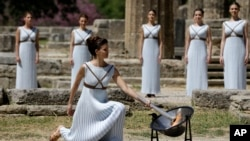 La llama olímpica fue encendida por la actriz Katerina Lehou, representando una suma sacerdotisa pagana, el miércoles 20 de abril de 2016, en la Antigua Olimpia, Grecia. Actress Katerina Lehou, right, as high priestess, lights the Olympic Flame, during the final dress rehearsal of the lighting of the Olympic flame at Ancient Olympia, in western Greece, April 20, 2016.