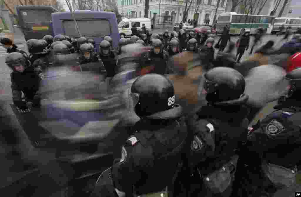 Pro-European Union activists pass through a police line as they march against the government in Kiev, Dec. 17, 2013.