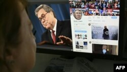 A photo illustration dated April 18, 2019 in Washington, D.C. shows an editor looking at a photograph of U.S. Attorney General William Barr (L) speaking about the release of the redacted version of the Mueller report, juxtaposed with U.S. President Donald Trump's Twitter feed.