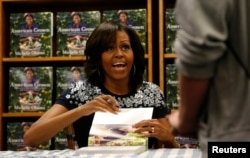 "U.S. first lady Michelle Obama looks up as she signs a copy of her book ""American Grown: The Story of the White House Kitchen Garden and Garden Across America"" at the Politics & Prose bookstore in Washington May 7, 2013. REUTERS/Kevin Lamarque (UNITED"