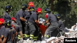 意大利救援人员从瓦砾堆中抬出一名地震遇难者。 (2016年8月25日)