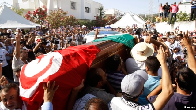 Mourners carried the coffin of slain opposition politician Mohamed Brahmi during part of his funeral procession in Tunis July 27, 2013.