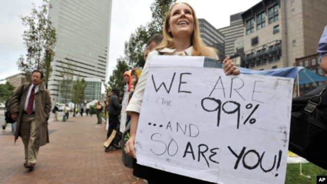 A woman who identified herself only as Jenna, and said she worked at an architecture firm in Boston's financial district, stops on her way to work to join demonstrators with Occupy Boston on Monday, Oct. 3, 2011.
