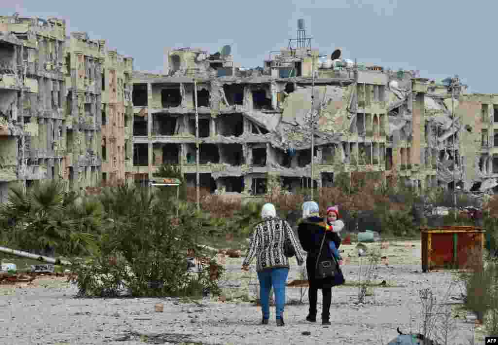 People who live in a neighborhood on the edge of the northern Syrian city of Aleppo return to their homes to check the damage caused by fighting between regime forces and rebel fighters.