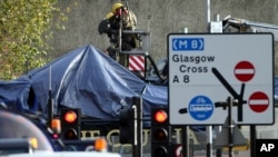 Petugas pemadam kebakaran dan penyelamatan Skotlandia di lokasi jatuhnya helikopter di Clutha Bar, Glasgow (30/11). (AP/Scott Heppell)