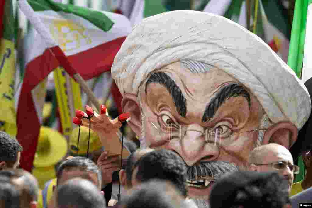 """Max Saatchi mengenakan topeng bergambar Presiden Iran Hassan Rouhani pada reli """"No to Rouhani, Yes to Human Rights in Iran"""" yang diselenggarakan oleh Dewan Nasional Perlawanan Iran, di luar markas besar PBB di New York, di sela-sela Sidang Majelis Umum PBB."""