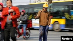 A worker crossing a street in Beijing, March 22, 2013.
