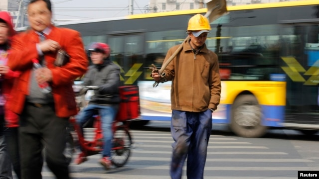 A worker crossing a street in Beijing, March 22, 2013.