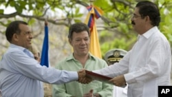 Honduras' President Porfirio Lobo, left, and Honduras' ousted President Manuel Zelaya, right, shake hands after signing an agreement as Colombia's President Juan Manuel Santos applauds in Cartagena, Colombia, May 22, 2011