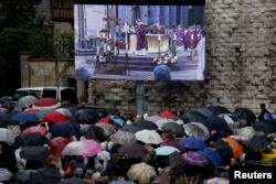 Mourners gather in the rain near a giant screen outside the Cathedral in Rouen, France, during a funeral service in memory of slain French parish priest Father Jacques Hamel at the Cathedral in Rouen, France, Aug. 2, 2016.