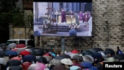 Une foule rassemblée devant un écran géant suit les obsèques du Père Jacques Hamel, curé français tué à la cathédrale de Rouen, France, 2 Août 2016.