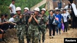 중국 윈난성 지진 피해 현장에서 4일 구조요원들이 부상한 주민을 병원으로 대피소로 옮기고 있다.