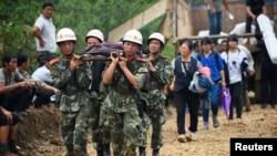 Nhân viên cứu hộ khiêng người bị thương trên cáng tại thị trấn thị trấn Long Đầu Sơn của huyện Lư Điền, ngày 4/8/2014.