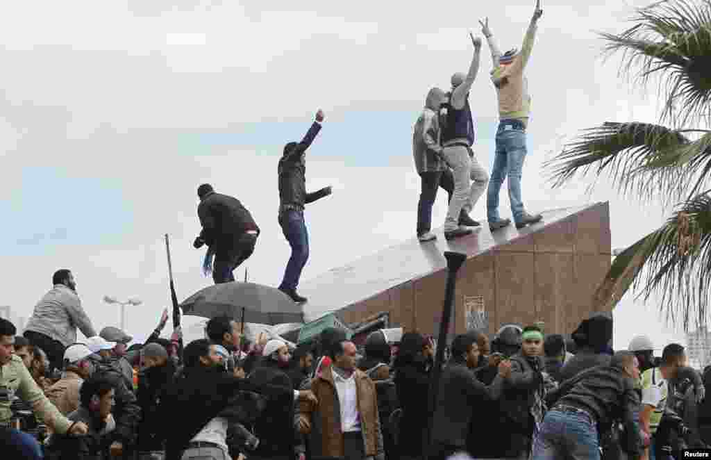 Protesters supporting Egyptian President Mohamed Morsi gesture as anti-Morsi protesters throw rocks at them during clashes in Alexandria, Egypt, December 21, 2012.