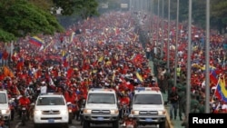 Thousands of people follow the funeral parade of Venezuela's late President Hugo Chavez in Caracas, March 15, 2013.