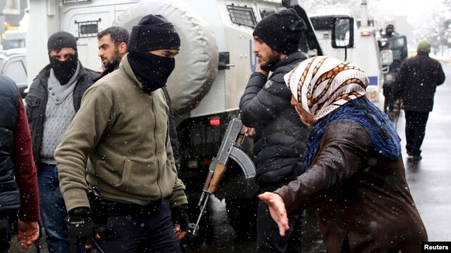A Kurdish demonstrator argues with members of Turkish police special forces during a protest against the curfew in Sur district and security operations in the region, in the southeastern city of Diyarbakir, Turkey December 31, 2015.