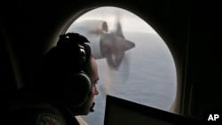 Petugas di atas pesawat Angkatan Udara Australia yang mencari pesawat Malaysia Airlines Penerbangan MH370 di bagian selatan Samudera Hindia, 2014. (AP/Rob Griffith)