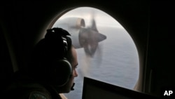 In this March 22, 2014 file photo, a flight officer aboard a Royal Australian Air Force plane searches for signs of missing Malaysia Airlines Flight MH370 in the southern Indian Ocean off Australia.