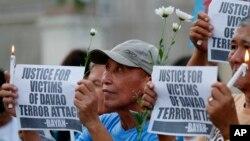Người biểu tình cầu nguyện cho nạn nhân vụ đánh bom khủng bố do nhóm phiến quân Abu Sayyaf thực hiện ở Davao tháng 9 năm ngoái. Nhóm phiến quân này cũng được cho là đứng sau vụ chặt đầu con tin người Việt.