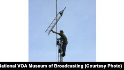 Mike Murphy of KA8ABR in Dayton adjusts the top of a radio antenna on the campus of the National VOA Museum of Broadcasting
