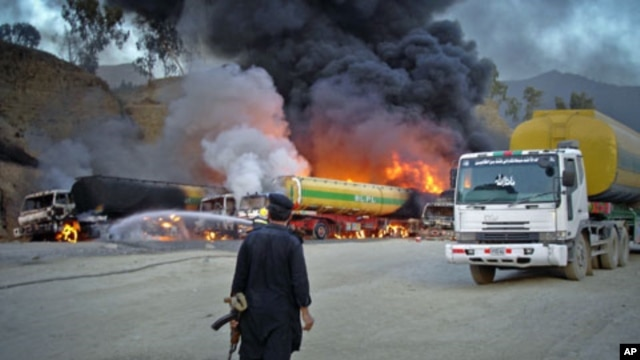 A security official stands near oil tankers - carrying fuel to US-led NATO forces in the northwestern tribal region of Khyber - that were set ablaze by a bomb blast near the main border crossing of Torkham, on the outskirts of Landikotal in Afghanistan, J