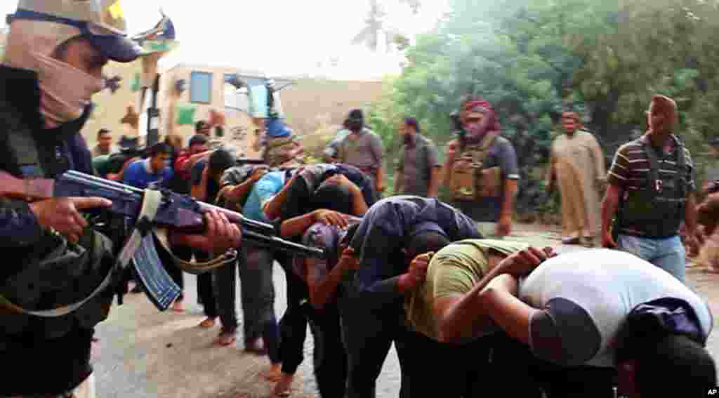 This image posted on a militant website on June 14, 2014 appears to show militants from the Islamic State of Iraq and the Levant with captured Iraqi soldiers wearing plain clothes after taking over a base in Tikrit, Iraq.