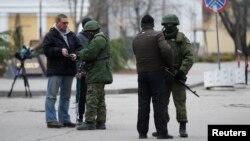 Petugas memeriksa dokumen dua orang jurnalis di dekat gedung parlemen di Simferopol, Krimea (foto: dok).