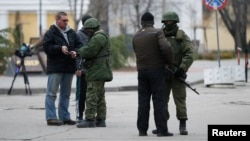 FILE - Armed men check journalists' documents around the regional parliament building in the Crimean city of Simferopol, March 1, 2014.
