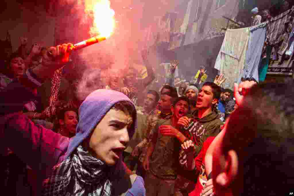 An Egyptian youth carries a lit flare as supporters of the Muslim Brotherhood gather in the El-Mataria neighborhood of Cairo, to protest the 20-year sentence for ousted president Mohammed Morsi and verdicts against other prominent figures of the Brotherhood.