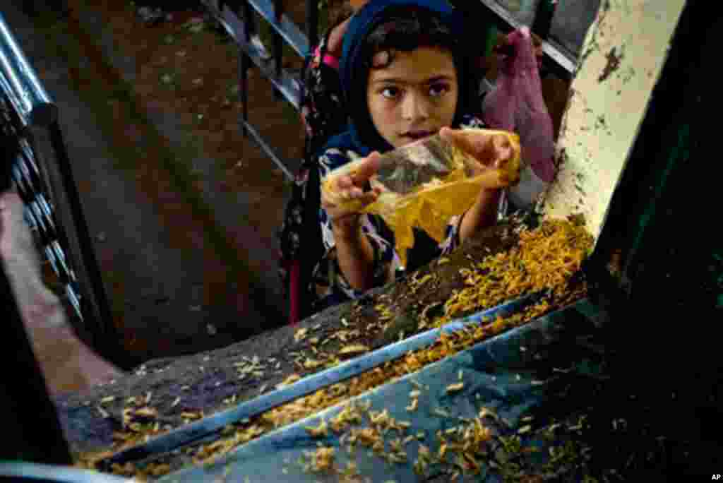 A Pakistani girl receives free food from a food distribution point at the shrine of Bari Imam on World Food Day in Islamabad, Pakistan on Oct. 16, 2010. According to World Food Program report, almost half the population of Pakistan faces difficulty gainin
