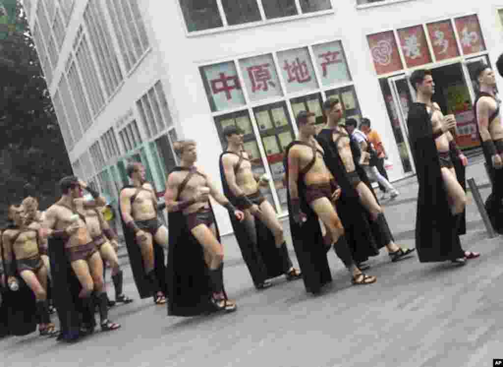 Men dressed in Spartan-style costumes walk through a commercial plaza in Beijing, July 22, 2015. A salad store paraded dozens of half-naked Western men dressed as Spartans through China's capital as a publicity stunt, drawing a crackdown by police who were photographed restraining some of them on the ground.