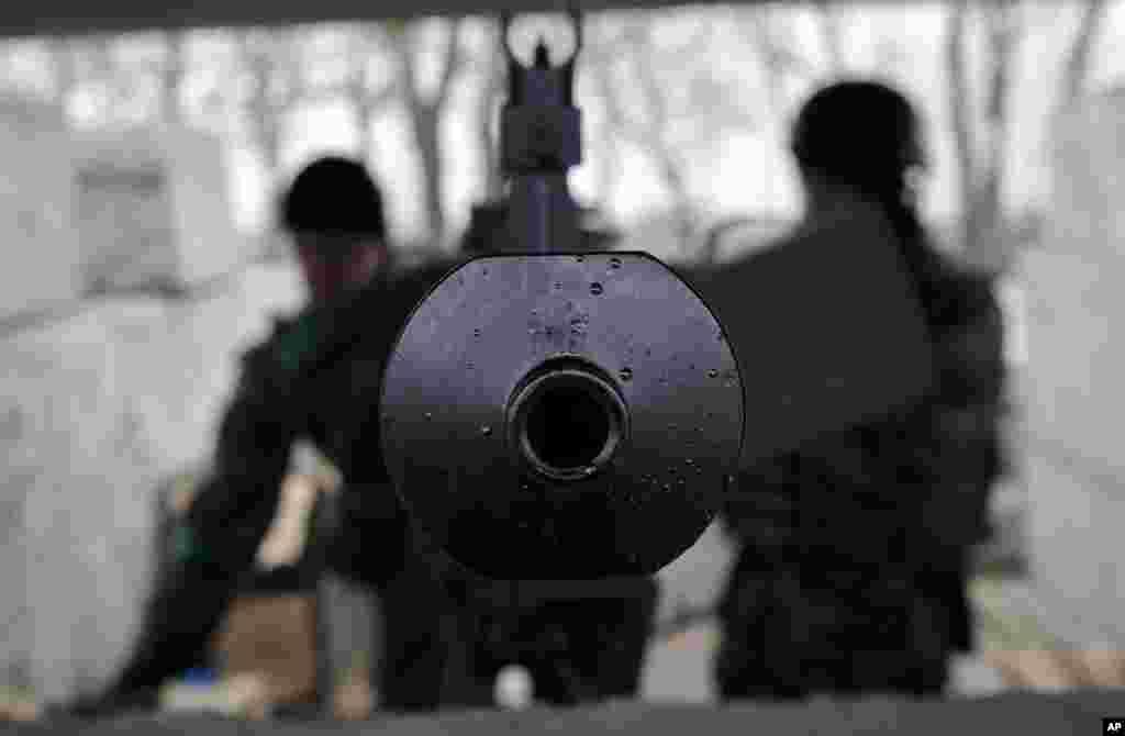 Servicemen stand inside a heavy machine-gun position at a Ukrainian army checkpoint near Kurakhove, Ukraine, March 3, 2015.