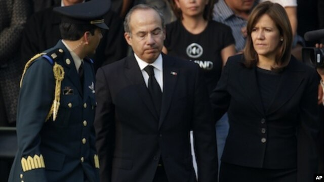 Mexico's President Felipe Calderon, center, reacts next to his wife Margarita Zavala after paying their respects to the relatives of the eight victims of a helicopter crash at the Campo de Marte military field in Mexico City, Thursday, Nov. 12, 2011.