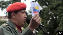 Venezuela's President Hugo Chavez talks to supporters as he holds a picture of an old Venezuelan flag during a ceremony in Caracas July 14, 2011.