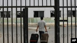 A Palestinian man carries suitcases to the waiting hall before entering Egypt through the Rafah border crossing, southern Gaza Strip, June 8, 2011.
