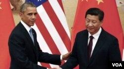 ປະທານາທິບໍດີ Barack Obama, ຊ້າຍ, ສຳພັດມືກັບ ປະທານປະເທດຈີນ ທ່ານ Xi Jinping.