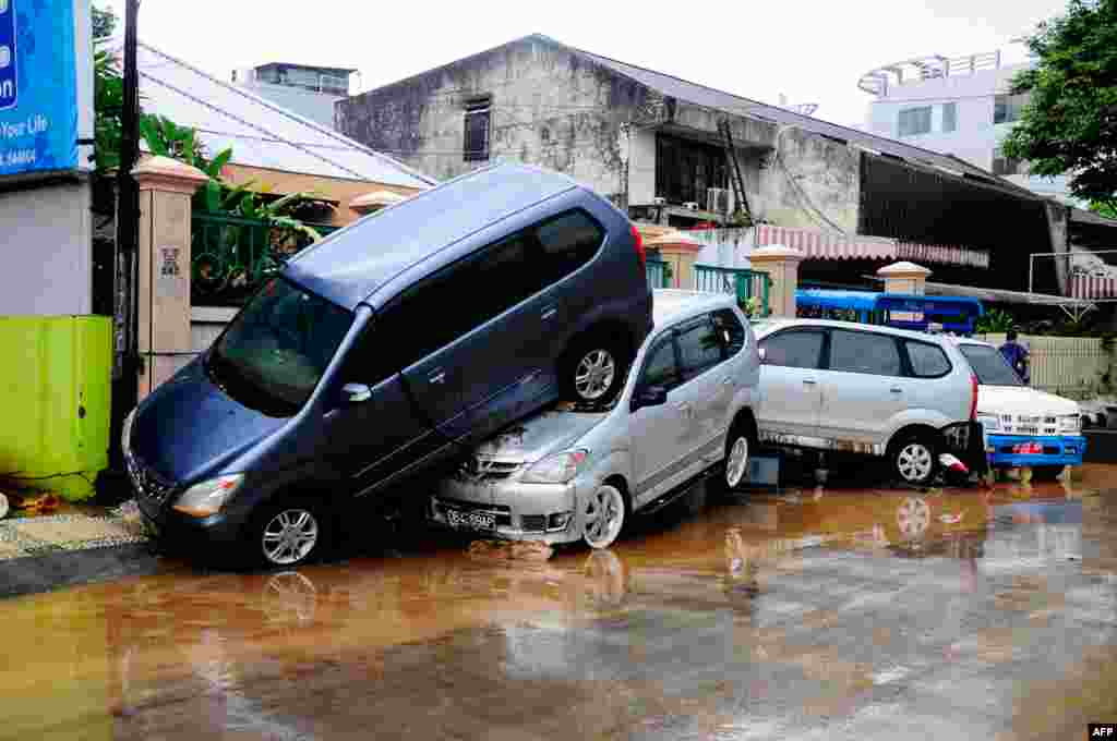 Cars are seen on top of each other after being hit by flood waters in Manado. At least 13 people were killed after overnight flash floods and landslides hit Indonesia's Sulawesi island, an official said.