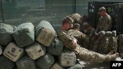 Американський солдат сидить на багажі, готуючи до повернення з Афганістану.