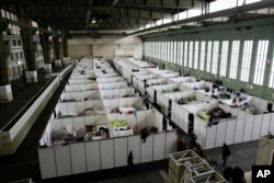 FILE - Cabins are set up inside Hanger 4 of the former airport Tempelhof to be used as a temporary emergency shelter for migrants, refugees and asylum seekers in Berlin, Dec. 9, 2015. The number of migrants entering Germany has dropped significantly in the last few weeks.