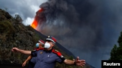Police officers block a road as lava rises following the eruption of a volcano on the Island of La Palma, in Tacande, Spain, September 22, 2021.